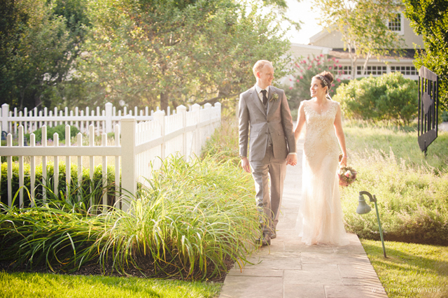 Bride-and-groom-stroll-in-cottage-garden-by-W-Studios-New-York